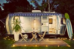 Architecture Ideas, Romantic Airstream Trailer With Blue Awning, Blue Stripe, Surfing Bord, And Outdoor Diniing Table: Awesome Classic Refurbished Airstream Trailer for Sale