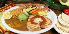 Pollo Acapulco - Grilled chicken breast, four Gulf shrimp. Topped with Salsa Ranchera and Monterrey cheese, served with grilled vegetables, Guacamole, beans and rice.