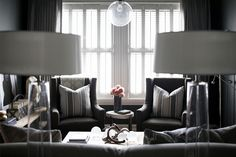 Living room with a balanced symmetry in grey, charcoal, silver, and white.  Cozy and sophisticated.
