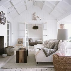 Modern country beach house neutrals and textures...white linen sofa, white painted hardwood floors, wicker side table, mod reclaimed wood bench as a coffee table. sisal rug, white exposed beams on ceiling...