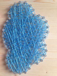 Ahşap üzerine çiviler ve renkli ipler kullanılarak yapılan string art tasarımı.
