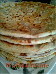 Bonjour a tous, aujourd'hui je vous propose une recette traditionnelle algérienne, assez proche des Mhajeb ou de la Kesra bedwa (recette a venir prochainement), une galette a base de semoule farcie aux tomates séchées et aux oignions verts. Ingrédients:...