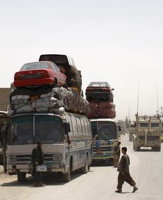 Passenger buses are loaded with cars for transport in Kandahar