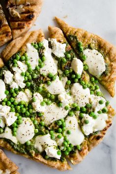 A bountiful spring Pesto Pea Pizza made with a basil vinaigrette, fresh mozzarella, ricotta cheese and blanched spring peas