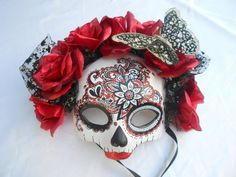Beautifully hand painted Day of the Dead skull mask, hand formed out of light weight paper clay. Red silk flowers and a faux black butterfly frame the mask making it very impressive. One of a kind and comes with a certificate of authenticity.  Great for Cinco De Mayo, Day of the Dead, Halloween, Masquerade parties or makes for wonderful decoration.