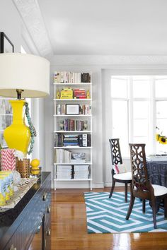 White Dining Room - A bookcase and high-backed dining chairs atop a patterned rug
