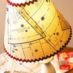 """Sewing Embellishments lampshade! Clever! Use spray adhesive to attach patterns to a shade in a random fashion. Trim excess paper. Adhere rickrack to the top and bottom edges of the shade."""" (from BH)"""