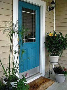 beige house exterior with teal front door | Benjamin Moore Calypso Blue Turquoise Front Door
