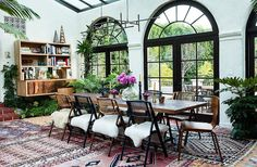 Layered kilim and Moroccan rugs and chairs topped with sheepskins add major bohemian attitude to this outdoor dining space.