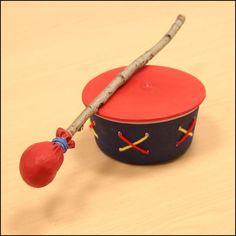 Materials  two balloons  a round plastic container  two elastic bands  art supplies to decorate the drum (optional)  piece of material for stuffing  stick or tree branch measuring about ½ inch in diameter, and 12 inches long  string or wool (optional)  Instructions