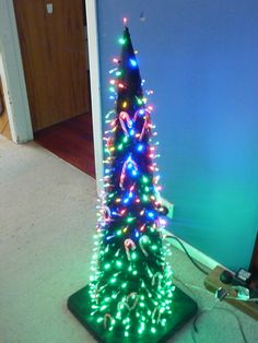 Road Cone + Spray Paint + Electric Drill + Few Hundred lights = Christmas Tree