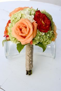 Two tones of orange roses, green hydrangea and hanging amaranths.