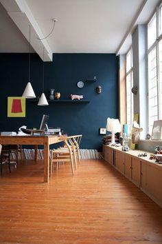 salle à manger au mur bleu canard , fenêtre en vitrail , vieux plancher sapin , longue table en bois et chaises scandinaves