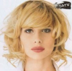 Medium length blonde with tousled curls and dark roots and side swept bangs hairstyle