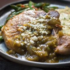 Mexican pork chops recipe with chile verde sauce and cotija cheese served with mexican green beans and tomatoes and cheesy cauliflower mash on a dark handmade plate.
