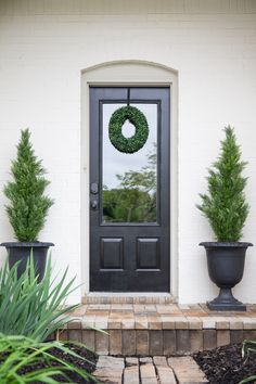 Love this front door entrance (and those potted trees are fake - no maintenance required)!  #curbappeal #landscapingideas #frontdoordecor