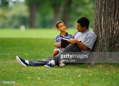 128393785-father-and-son-sit-by-tree-in-park-and-read-gettyimages.jpg (487×352)