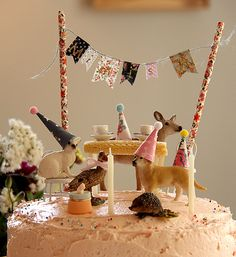 adorable party on top of the cake - little creatures with sweets and a bunting on straws