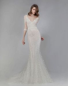 Victoria KyriaKides mermaid style wedding dress with polka dot floral appliques and sheer half-sleeves