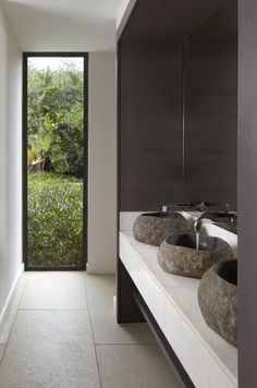The natural stone basins look just perfect, the organic shape gives this space a casual spa feel.