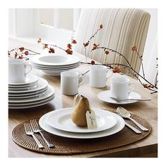 this is a typical table setting found in japan. this setting includes plates, cutlery, cups, and elegant chairs.