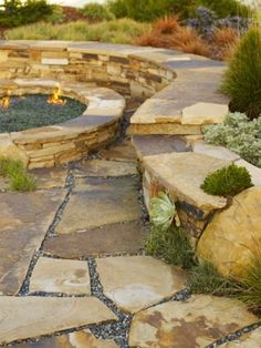 love the flagstone with pea gravel & the stacked stone wall around the fire-pit