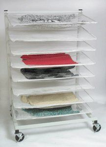 """Sweater Drying Rack by Cleaner's Supply®. $149.00. Don't have the space to air dry sweaters? Don't sweat it! Our Sweater Drying Rack uses casters and 8 removable shelves to create a whole new space for air drying. White mesh covering allows air to flow naturally through each sweater for faster drying. Made with high-quality steel tubing and extra front and rear cross bracing for better stability. Powder coated for a durable white finish. Size: 37""""(L)x26""""(W)x53""""(H)."""