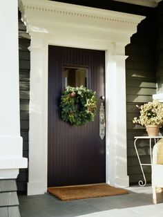 This is a Statement Door!  Love it.    Small and Simple  The beautiful simplicity of this front door and porch calls for something equally as calm for the holiday season. A natural green wreath with scattered pinecones is the perfect holiday decor for this home.