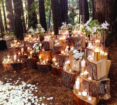 Woodland ceremony decor with logs and candles A Dreamy Glow  An illuminated ceremony altar adds a romantic glow to an outdoor ceremony during any season. Created with only tree stumps and candles, this setting looks simply gorgeous for a woodland wedding.Looking for more woodsy wedding ideas Find more inspiration in tmountain wedding details andwoodland table picks