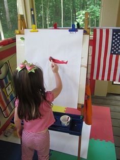Prop a flag at the easel to inspire preschoolers. You don't even need to announce that we're making flags today. You might notice some stripes being formed...