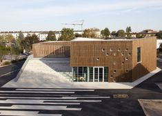Bleachers climb over the roof of this timber-clad community centre in France by Ateliers O-S Architectes