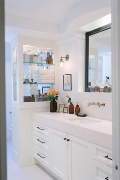 Well appointed white and black bathroom features a white washstand contrasted with oil rubbed bronze hardware and fitted with a thick white quartz countertop holding a rectangular sink under a satin nickel faucet mounted on a white quartz backsplash beneath a black framed mirror fixed in a niche flanked by satin nickel down-light sconces mounted above a framed art piece and beside a built in glass linen cabinets.