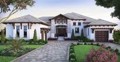 <div><ul><li>Decorative wood trim, transom windows and a gorgeous roof line elevate the curb appeal of this exceptional Florida house plan.</li><li>The foyer has front to back views of the entry and the covered lanai with lots of glass to brighten this entrance.</li><li>To the left is a private bedroom and bathroom while the right side takes you into the enormous great room area that combines the dining room, kitchen and great room, with won...