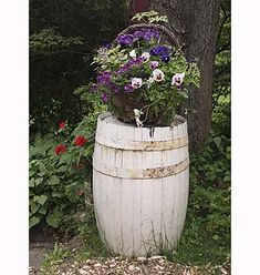 A retired rain barrel positioned in a shady corner of the yard boosts up a basket overflowing with (clockwise from center, right) purple and white pansies, easy-care calibrachoa ('Million Bells Plum'), variegated oregano, deep-purple verbena, and lacy ferns. | Photo: Nancy Andrews | thisoldhouse.com