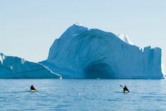Tourists sea kayaking past an iceberg, Hall Bredning, Renland, Greenland, on the 20 August 2007.