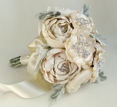This silk fabric bridal bouquet is comprised of hand cut and formed silk fabric flowers of various shades of cream and ivory. Each flower has its own hand placed highlights featuring either rhinestones, crystals or genuine freshwater pearls. Completely handmade and stunning!Also features soft handmade silk velvet dusty miller leaves.Measures about 8 1/2 inches (21.59 centimeters) in diameter and 11 inches (28 centimeters) long with a nicely domed head.Takes many hours to...