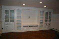 built ins for TV wall, storage for kids toy baskets, their crafts, etc...  Maybe 18-20 inches deep.  No glass, just solid door fronts & where there is open shelving make one long solid door.  Make TV opening smaller for a smaller TV and add more drawers under.