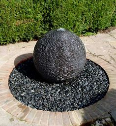 Dark Planet water ball fountain in circle of pebbles