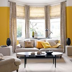 Zesty yellow living room with bay window This room is all about balance and symmetry of furniture, accessories and colour. We love the way this bold, mustardy yellow brings life to an otherwise neutral living room scheme. Scatter cushions on the sofa draw inspiration from the wall colour, pulling the sophisticated look together beautifully.