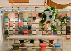 A patchwork of blue and green materials covers the exterior, while red and orange tones are used inside. The interior also features rounded seats and small tables, upholstered in Kvadrat textiles. A bicycle dressed in a yellow cover is parked by the door. Exhibition Display, Exhibition Space, Visual Merchandising, Werner Aisslinger, Building A Cabin, Fabric Display, Cologne Germany, Color Collage, Design Furniture