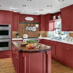 Barn-red Wood-Mode cabinets and walnut and marble counters. This Old House.