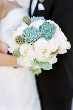 A tight bouquet of white peonies, dusty miller, scabiosa pods and succulents | @rachelannphoto | Brides.com
