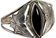 Navajo sterling silver cuff bracelet set with black onyx. Side fans are stamp-decorated with spiderweb design. Interior, 5 3/8 circumference, with