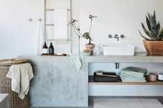 The cool, stone-coloured benchtop and weathered wood laundry basket makes this modern bathroom a little bit mid-western and a little bit amazing.