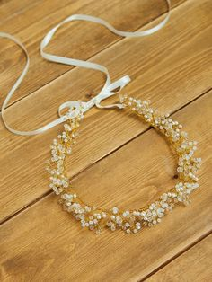 A lush golden hair wreath of delicately hand-spun wire is budding with a mixture of Swarovski crystals, frosted and glassy buds. This Grecian style
