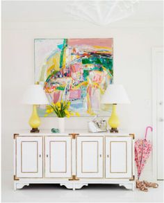 gold & white sideboard, abstract art, yellow lamps