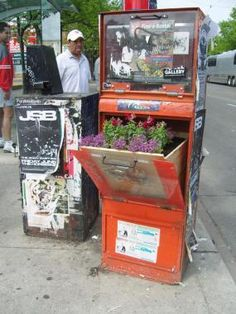 guerilla garden flower box  Toronto street artist PosterChild is currently working on an extensive project to convert flier and newspaper boxes into guerilla gardening boxes.