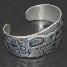This bracelet is designed by Jack Hudson, a Tsimshian from Metlakatla. He is a member of the Wolf Clan. The design presents the wolf, with the signature mark of flaring nostrils. The width is 1-1/4 inches, devolved length 6-3/4 inches. Sterling silve
