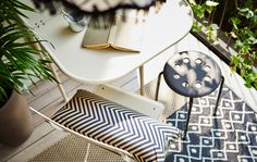 A shot from above on a balcony of a cup of coffee and book on a table, a couple of chairs and two rugs layered on the floor.
