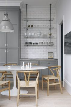 Susan Greenleaf San Francisco Home - A kitchen with gray cabinetry, open shelving, white subway tile, a Saarinen table, and Hans Wegner Wish...